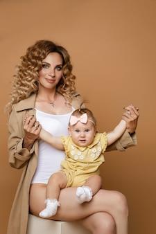 웃는 딸과 함께 앉아 흰색 바디 수트와 베이지색 코트에 진정 아름 다운 여자. 가족 개념
