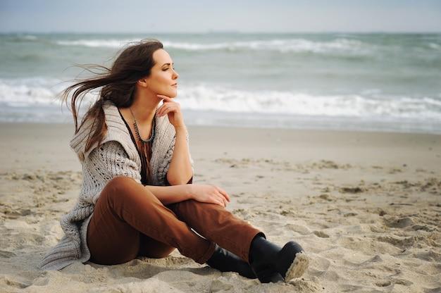 Спокойная красивая женщина сидит одна на песчаном пляже и смотрит на воду