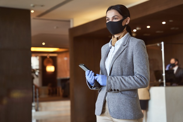 Calm beautiful woman standing in the lobby with a tablet in hands and looking into the distance