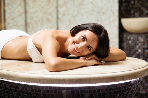 슬림 한 몸매와 건강한 피부를 가진 진정 아름다운 젊은 갈색 머리 여자가 쉬고 있으며 터키 식 목욕탕이나 터키 식 목욕탕에서 스파 절차를 취합니다.