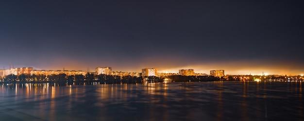 素晴らしいウクライナのドニプロペトロフスクの巨大な夜の明るい街の穏やかな大きな美しいドニエプル川