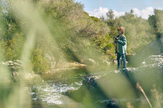 흐르는 강 근처 바위에 서 있는 사진 카메라와 함께 진정 소년
