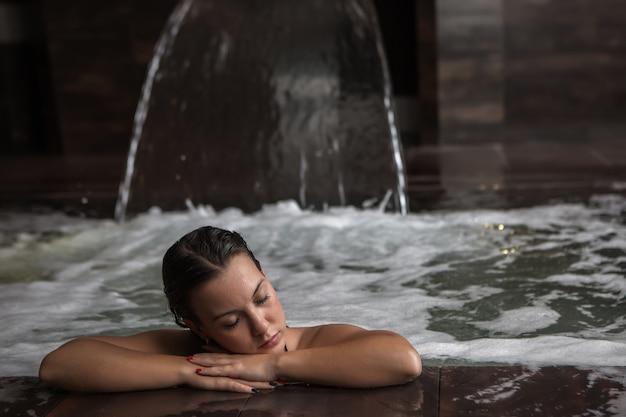 Спокойная брюнетка отдыхает в бурлящей воде спа-бассейна