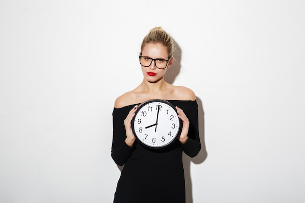Calm business woman in dress and eyeglasses holding clock