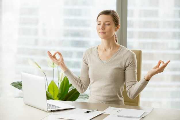 Спокойная деловая женщина расслабляется с дыхательной гимнастикой