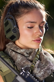 Calm caucasian armed female listen to walkie-talkie in headphones, in the forest