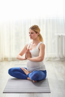Calm caucasian pregnant lady keep hands together meditating on floor