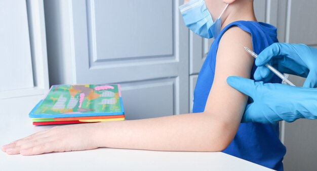 A calm child in a mask is vaccinated and watches an educational game
