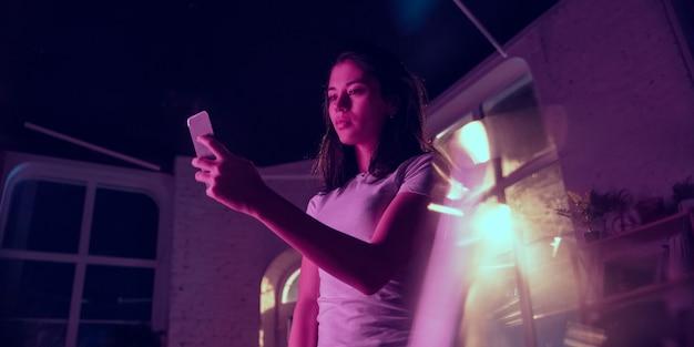 침착 한. 네온 조명이 켜진 실내에서 잘생긴 세련된 여성의 영화적 초상화. 보라색 - 파란색의 영화 효과처럼 톤. 실내에서 화려한 조명으로 스마트폰을 사용하는 백인 여성 모델. 전단.