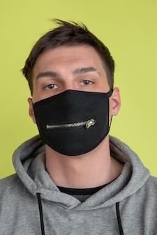 落ち着いて。黄色の壁に分離された白人男性の肖像画を閉じます。黒のフェイスマスクの気紛れな男性モデル。