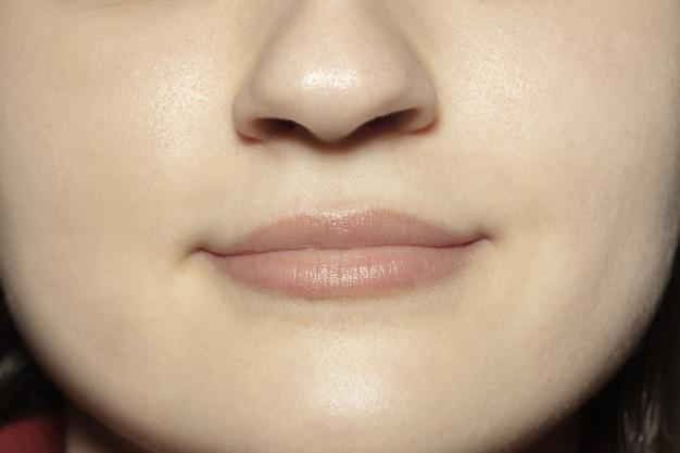 Спокойствие. снимок крупным планом женского рта с естественным блеском макияжа губ телесного цвета и ухоженной кожей щек.