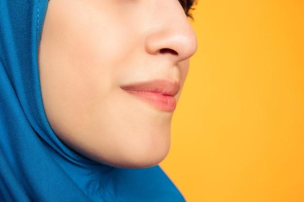 落ち着いて。黄色で隔離の若いイスラム教徒の女性を閉じます。