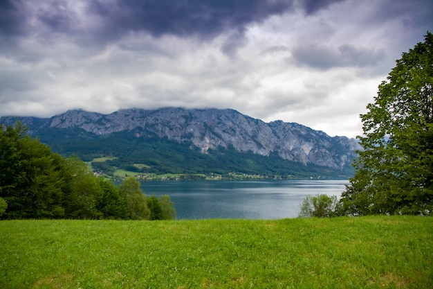 Calm cloudy day on lakefront of attersee with mountains in background in late summer. lake attersee in the austrian salzkammergut