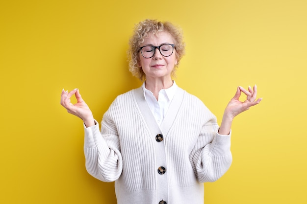 Calm confident aged woman in eyeglasses meditating isolated on yellow