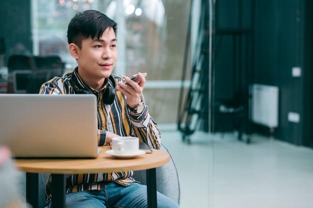 Спокойный уверенный в себе молодой человек сидит за столом со смартфоном в руке и записывает голосовые сообщения