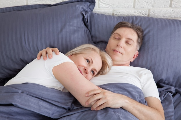 Calm couple sleeping and spooning in bed in bedroom at home.