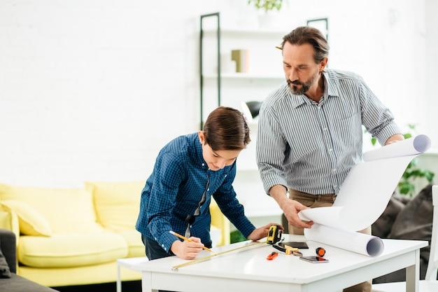 手に絵を持って立って、テーブルの長さをマークしている彼の笑顔の息子を見ている穏やかな好奇心旺盛なエンジニア