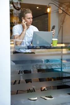 Спокойный кудрявый деловой человек с помощью смартфона, сидя за столом с портативным компьютером в кафе