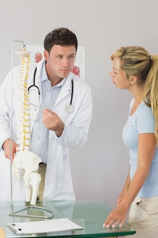 Calm doctor showing a patient something on skeleton model