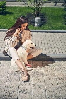 Спокойная собака сидит на краю тротуара с длинноволосой молодой кавказской женщиной