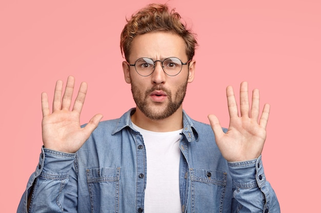 Calm down, please! handsome unshaven caucasian man keeps palms in front