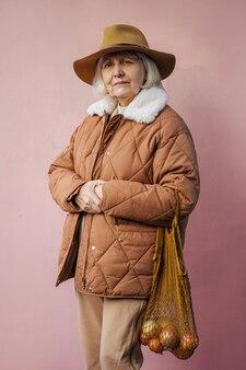 분홍색 벽에 식료품이 든 면 자루를 들고 세련된 겉옷을 입은 차분한 노인 여성.