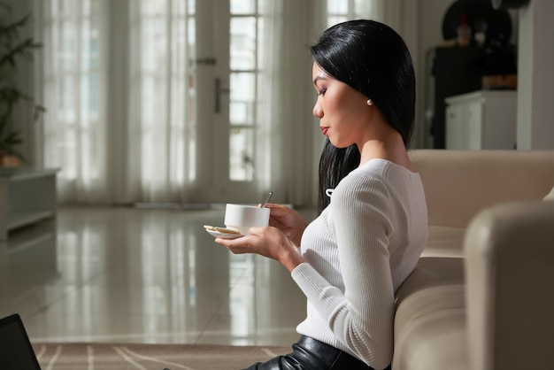 Calm elegant young asian woman with black hair sitting on floor and leaning on sofa while drinking coffee in living room