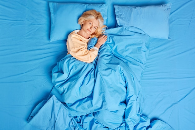 Calm european middle aged woman awakes satisfied after seeing good dreams poses well slept under blue blanket wears pajama feels comfortable enjoys lazy day. bed time and cozy morning concept