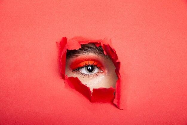 Спокойная женщина-модель с красными тенями для век смотрит сквозь рваную бумагу в студии