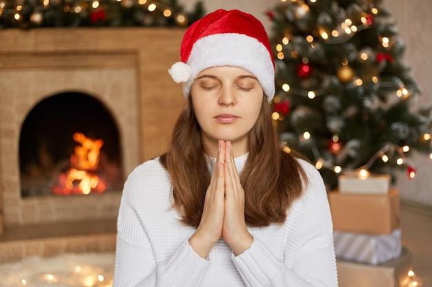 クリスマスツリーと暖炉の近くに屋内に座って、手のひらを一緒に保ち、より良い年を祈って、サンタクロースの帽子と白いセーターを着ている穏やかな女性は目を閉じています。