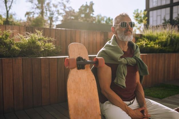 遠くを見ている木製のベンチに座ってサングラスをかけた落ち着いたフィットの成熟したスケートボーダー