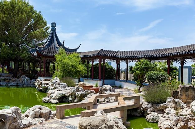 Calm garden, santa lucija 몰타의 석조 조각 정원과 호수가 있는 중국 전통 건축.