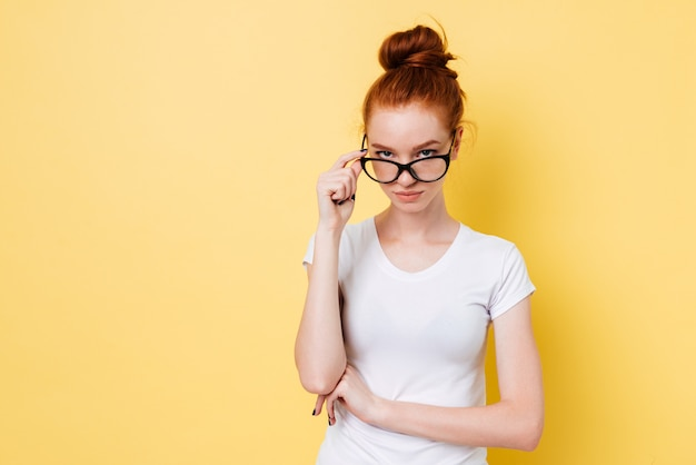 Calm ginger woman in eyeglasses looking through eyeglasses at camera