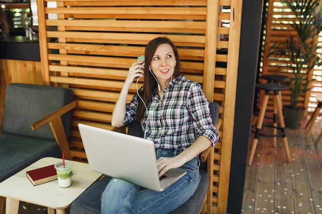Спокойная девушка на открытом воздухе, уличная летняя кофейня, деревянное кафе, сидя с на современном портативном компьютере, мобильном телефоне