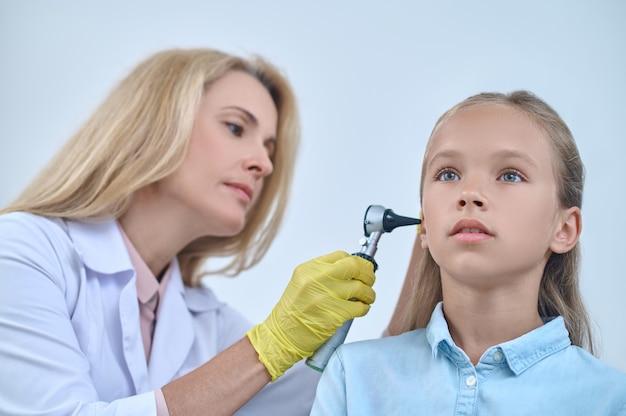 Calm girl and otolaryngologist with otoscope near ear