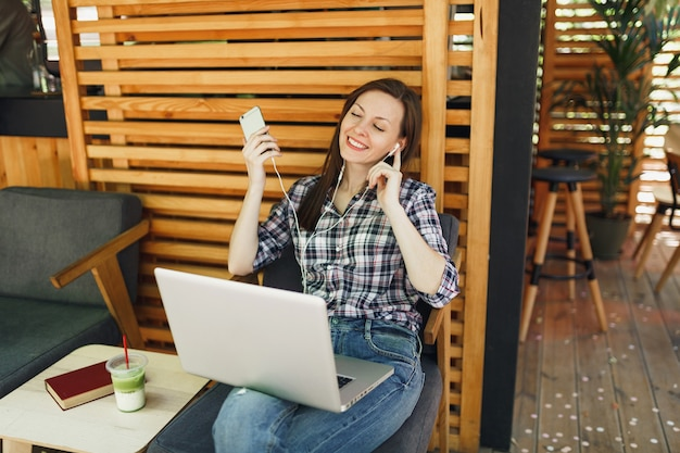 Calm girl in outdoors street summer coffee shop wooden cafe sitting with on modern laptop pc computer, cell phone
