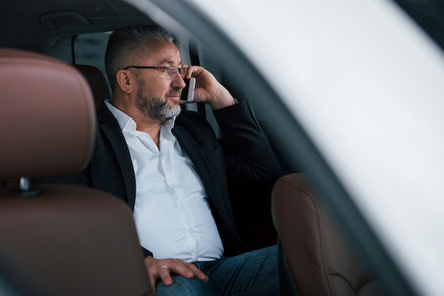 Calm and good mood. having business call while sitting at the back of modern luxury car. senior man in glasses and official wear