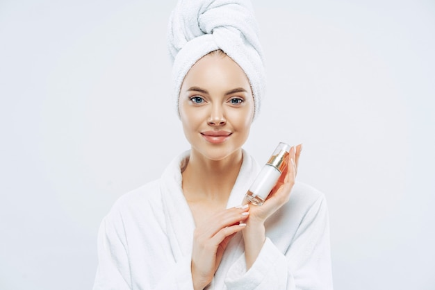 Calm gorgeous woman with healthy skin holds bottle of beauty body lotion