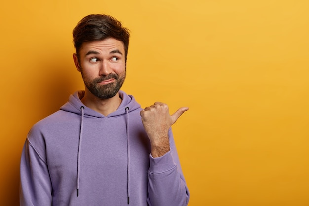 Calm handsome bearded caucasian man with curious expression points thumb aside on blank space, demonstrates good promo, place for your advertising, wears hoodie, poses over yellow  wall
