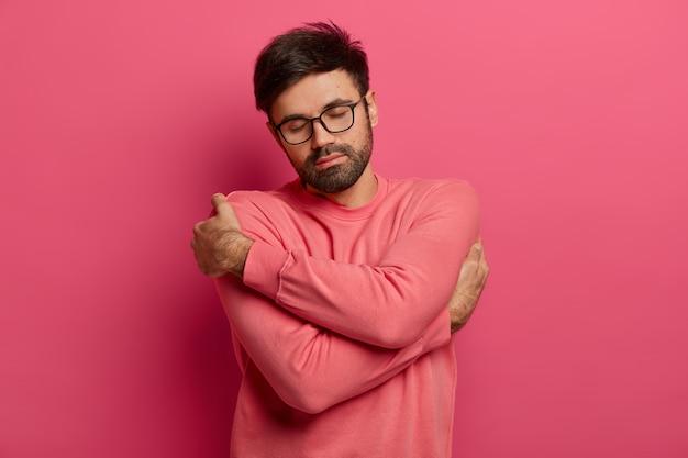 차분한 잘 생긴 수염 난 남자가 자신을 껴안고 편안하고 아늑함을 느끼고 여자 친구와의 낭만적 인 데이트를 회상하고 눈을 감고 머리를 기울이며 스웨터와 안경을 쓰고 분홍색 벽에 고립되었습니다. 무료 사진