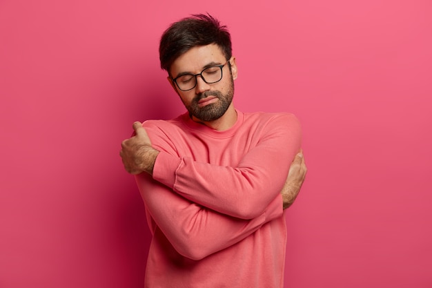 Calm handsome bearded man cuddles himself, feels comfort and coziness, recalls romantic date with girlfriend, closes eyes and tilts head, wears sweater and spectacles, isolated on pink wall