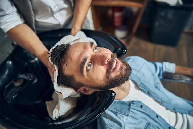 미용실에서 씻은 후 이발사가 수건으로 머리카락을 말리는 진정 잘 생긴 남자