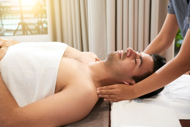 Calm handsome young man enjoying relaxing face, head and shoulders massage in spa salon