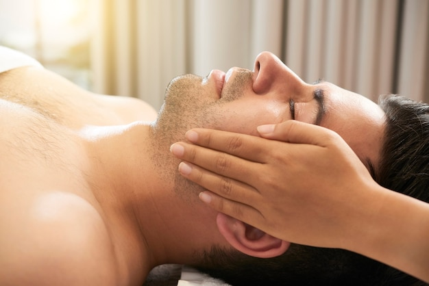 Calm handsome young man enjoying relaxing and rejuvenating face massage in beauty salon