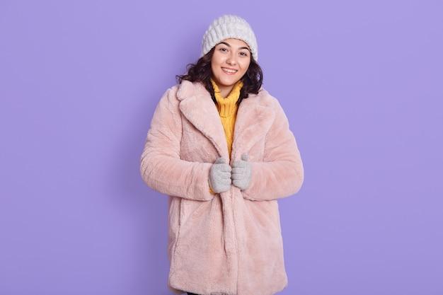 淡いピンクのフェイクファーのコートとキャップを身に着け、カメラを直接見て、喜びと幸せを表現し、薄紫色の背景の上に孤立して立っている穏やかな幸せなリラックスした女性。