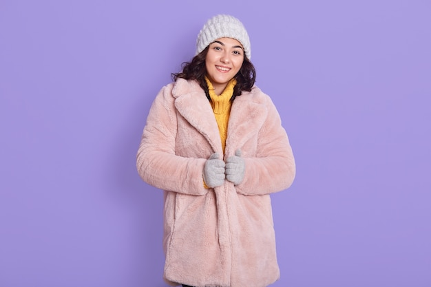 Calm happy relaxed lady wearing pale pink faux fur coat and cap, looking directly at camera, expressing joy and happiness, standing isolated over lilac background.