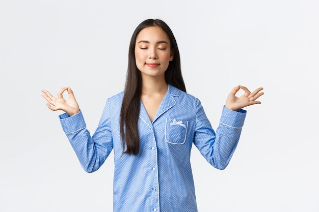 Calma e felice ragazza asiatica sorridente in pigiama blu chiudono gli occhi, meditando prima di dormire o al mattino, guardando sollevata e pacifica, pratica la meditazione yoga su sfondo bianco.