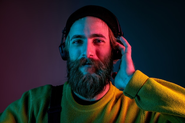 Calm, happy, smiling. caucasian man's portrait on gradient studio background in neon light. beautiful male model with hipster style in earphones. concept of human emotions, facial expression, ad.