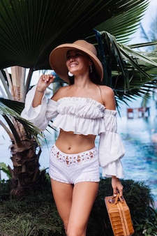 Calm happy stylish fashion girl wearing white knitted shorts and crop top with long sleeves holding picnic wicker basket handbag