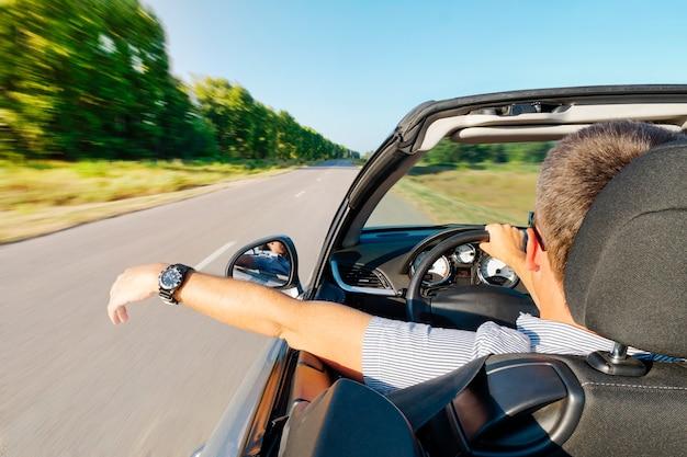 Calm happy successful man sit in the car hand is driving the car on the road. young guy inside an expensive convertible is driving on a road outside city against backdrop of beautiful summer nature.